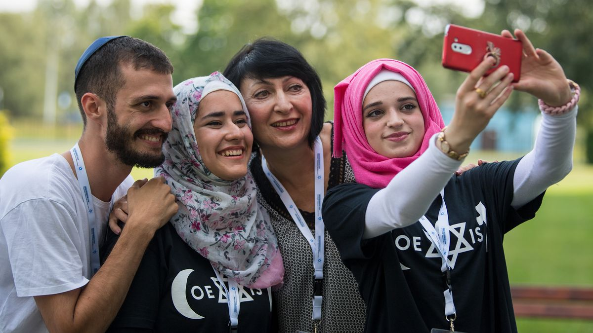 Zwei junge Muslimas mit Kopftuch und ein junger jüdischer Mann mit Kippa machen ein Selfie.