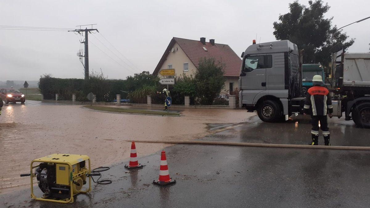 Die Feuerwehr sperrt eine überflutete Straße bei Westen im Kreis Straubing-Bogen