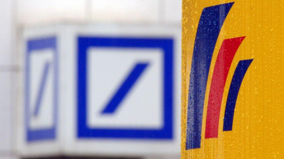 Das Logo einer Filiale der Deutschen Bank und das Logo der auf der gegenüberliegenden Straßenseite befindlichen Postbank-Zentrale.