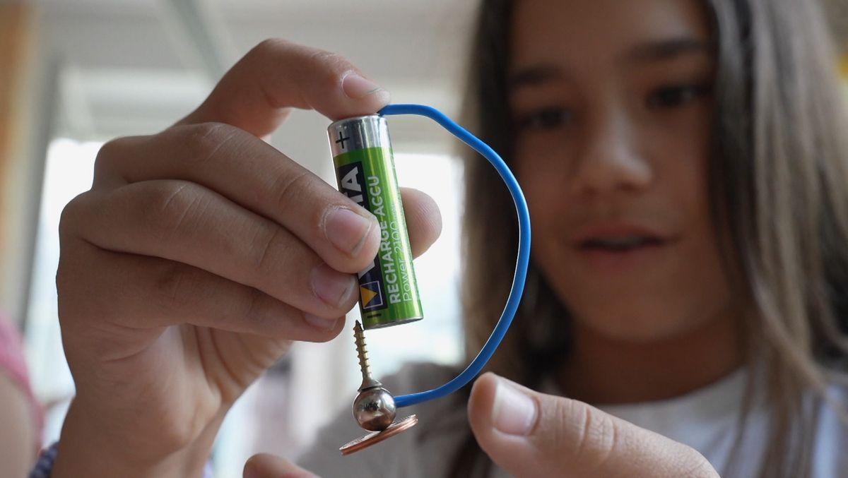 Schülerin hält einen Elektromotor aus einer Batterie, einem Stück Draht und einer Metallkugel
