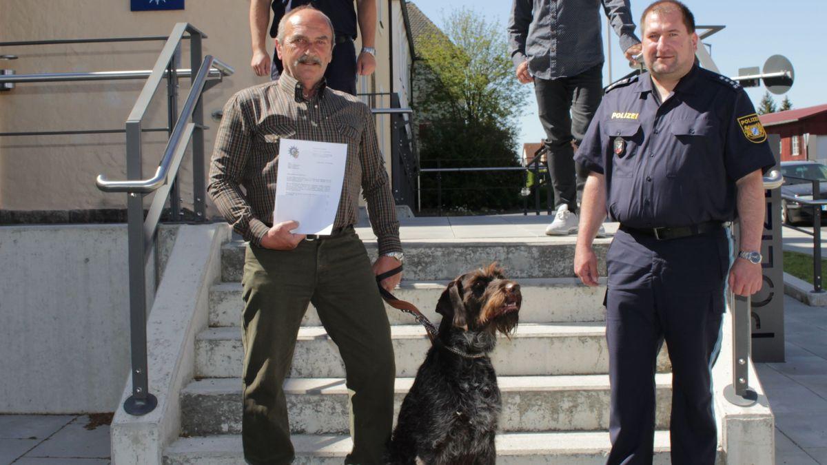 Eine links stehende Person hält einen Hund an der Leine, rechts eine weitere stehende Person.