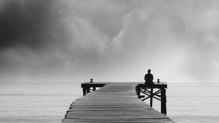 Symbolbild: Mann sitzt auf Steg und blickt aufs Wasser