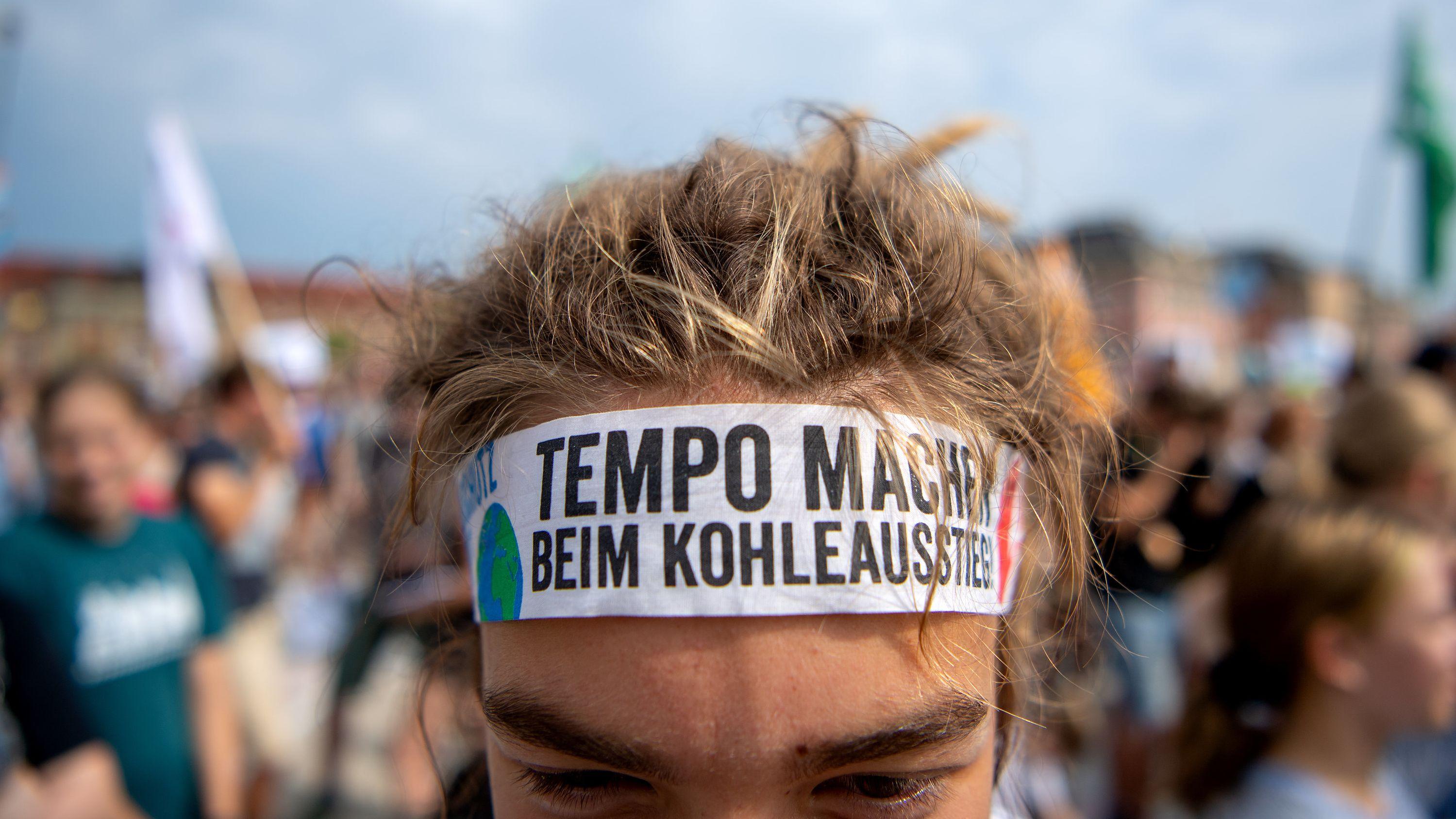 """Ein Schüler trägt bei der Klimademonstration """"Fridays for Future"""" im Lustgarten ein Stirnband mit der Aufschrift """"Tempo machen beim Kohleausstieg""""."""