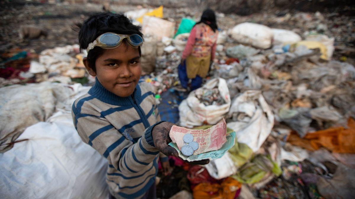 Ein Junge zeigt sein Geld, das er beim Müllsammeln verdient hat.