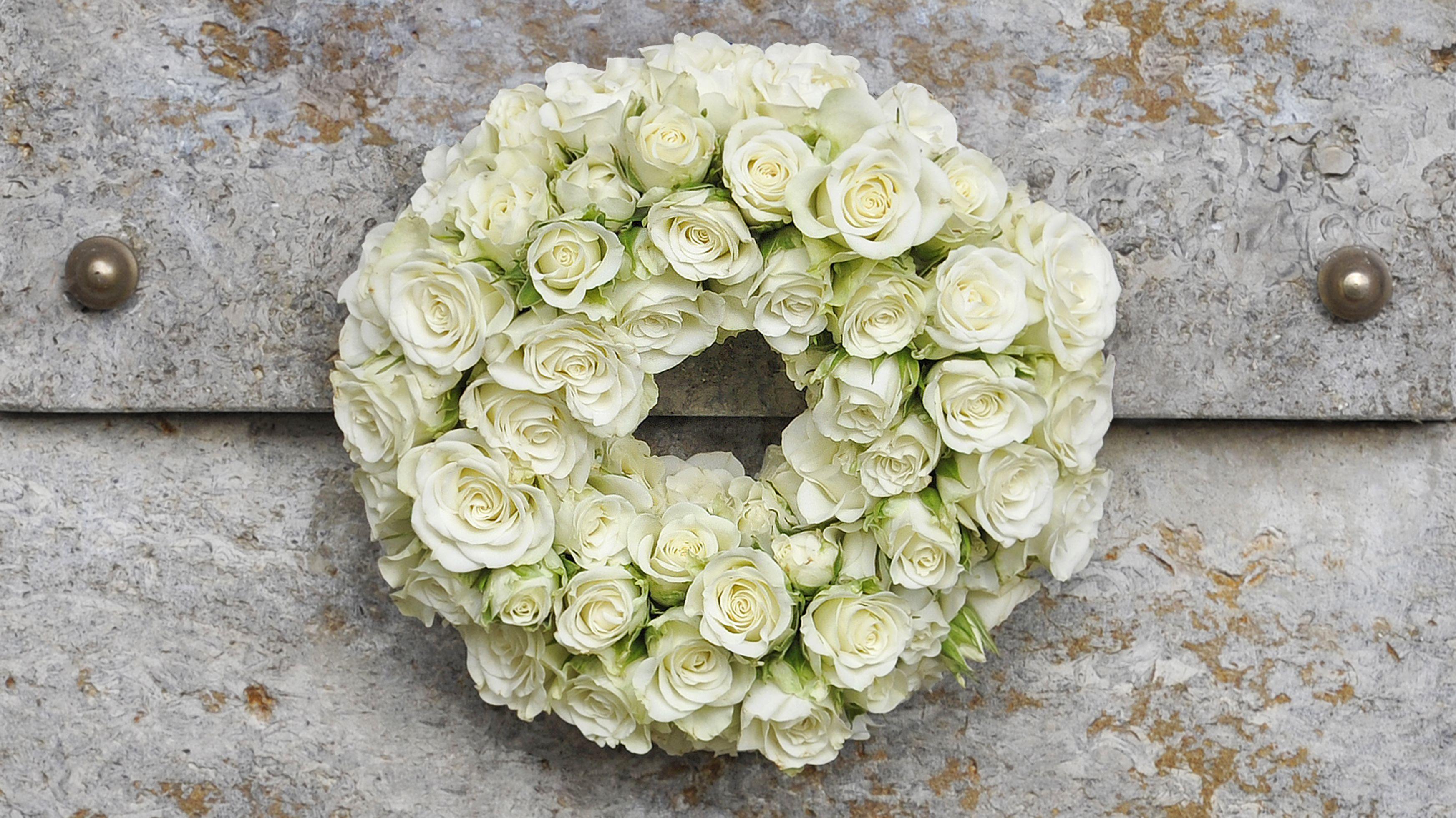 Blumenkranz auf einem Grab (Symbolbild)