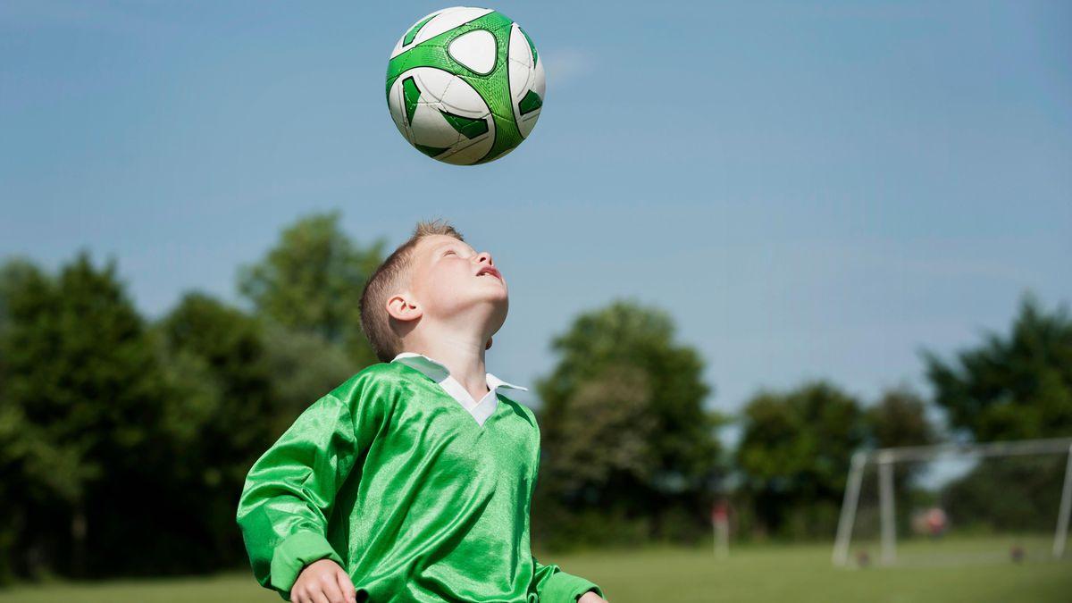 Kind trainiert Kopfbälle mit einem Fußball (Symbolbild)