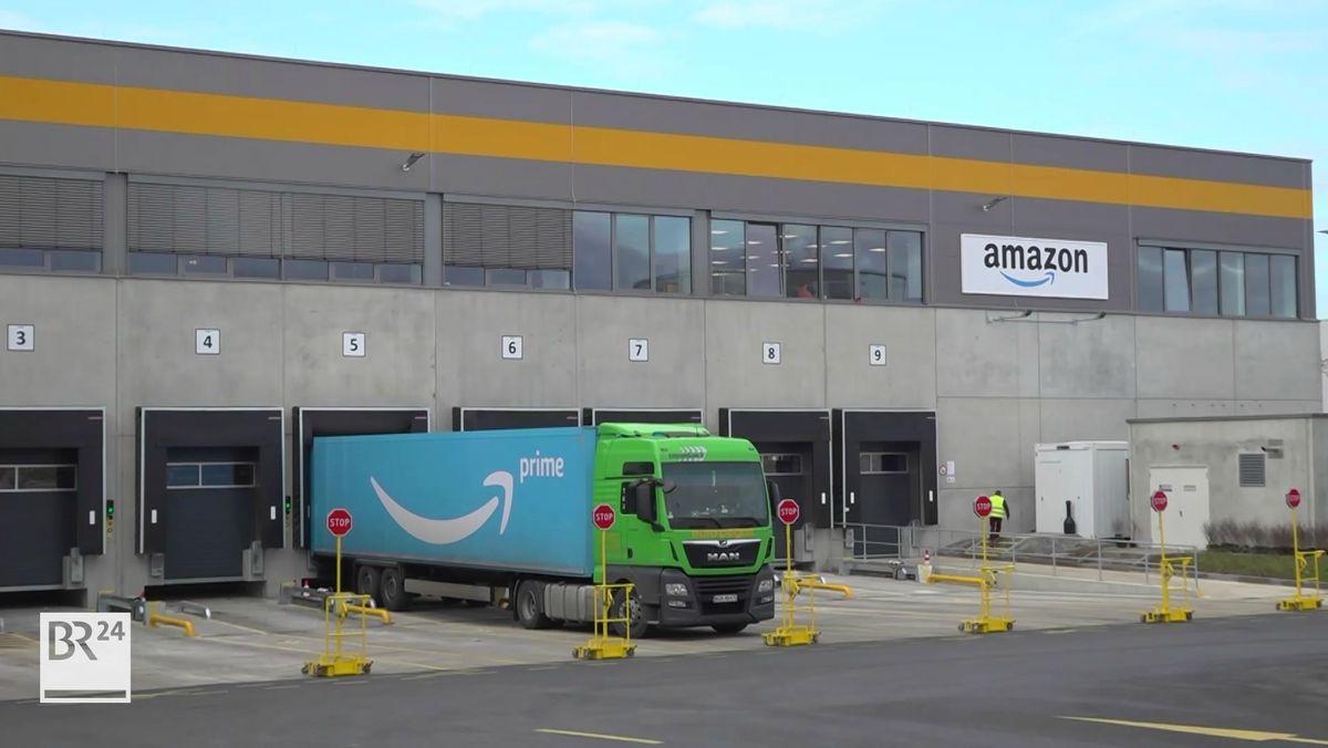 Ein Lastwagen parkt rückwärts vor einem Logistikzentrum, um beladen zu werden.