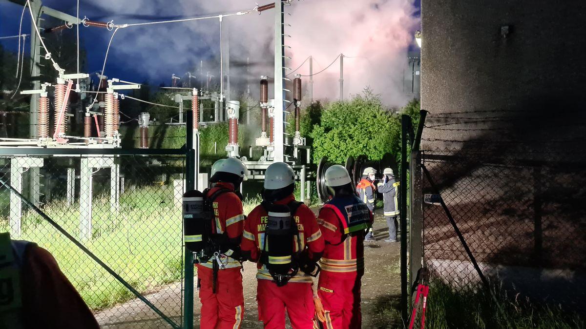 Feuerwehrleute in Anzügen, mit Helmen und Sauerstoffflaschen auf dem Rücken stehen auf dem Gelände einer Trafo-Station, die in Brand geraten ist.