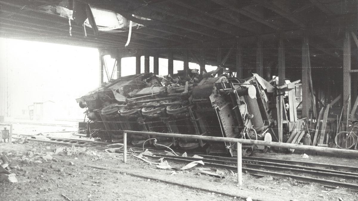 """Eine Rangierlok suchte am 27. Februar 1945 unter der sogenannten """"Gögginger Brücke"""" nahe des Augsburger Hauptbahnhofes Schutz vor den Luftangriffen. Doch eine Bombe durchschlug die Straßenfahrbahn und warf die schwere Dampflok um."""