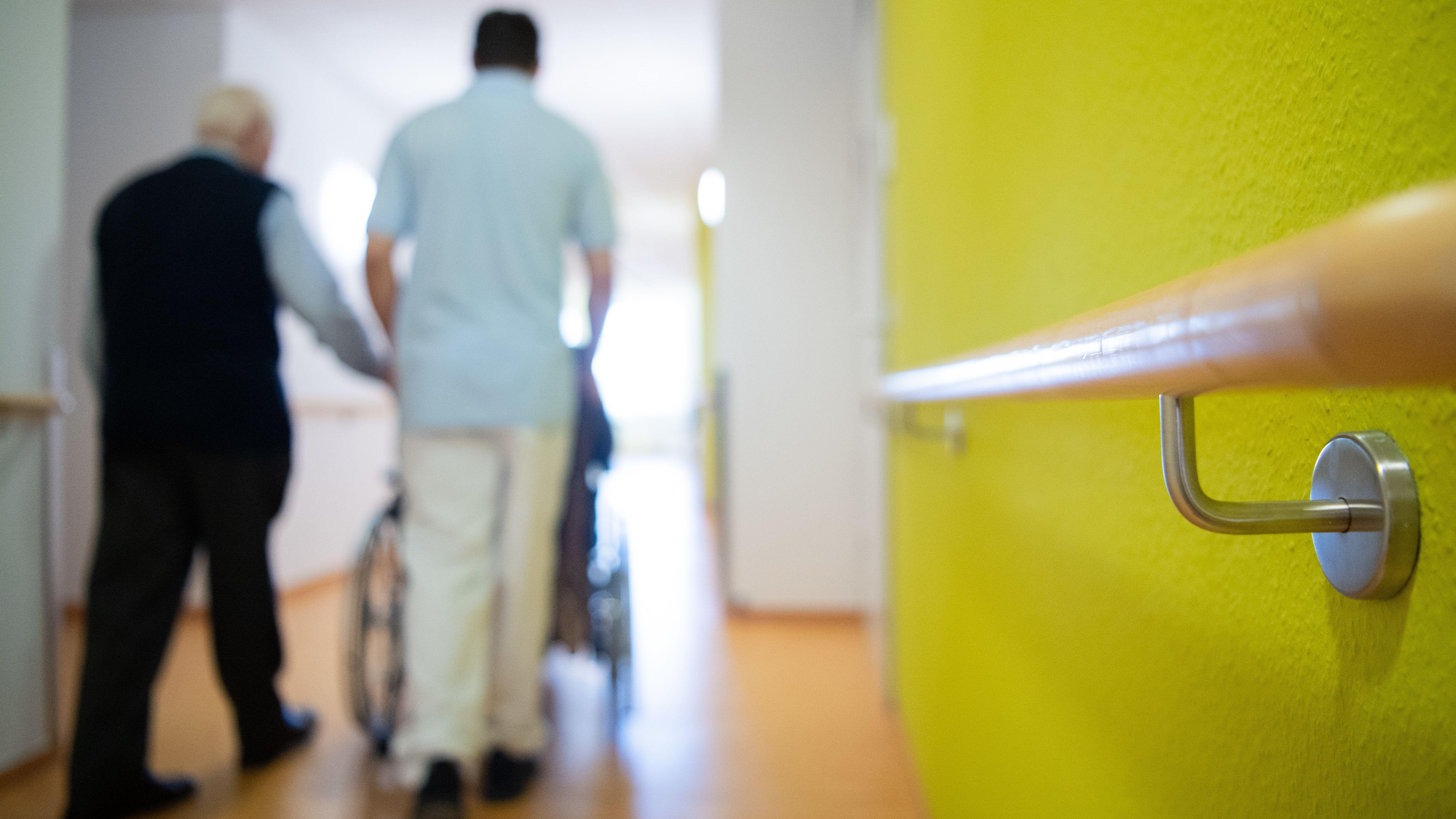Ein Pfleger läuft zusammen mit einem Bewohner des Pflegeheims über den Flur und schiebt einen Rollstuhl.