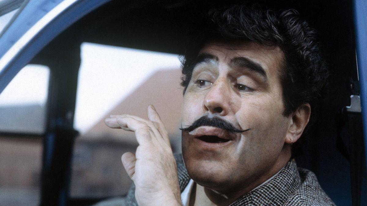 Mario Adorf trägt gezwirbelten Schnauzbart und sitzt in einem blauen Fahrzeug hinter'm Steuer.