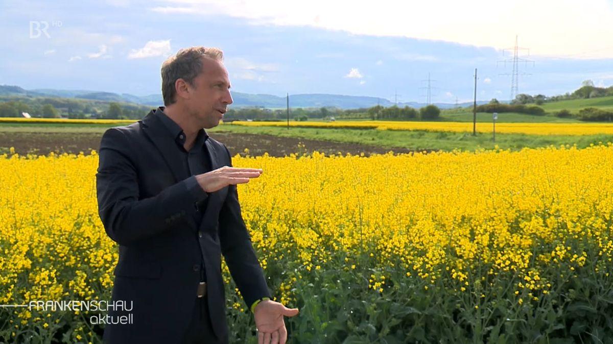 Bayerns Umweltminister Thorsten Glauber steht vor einem Feld.