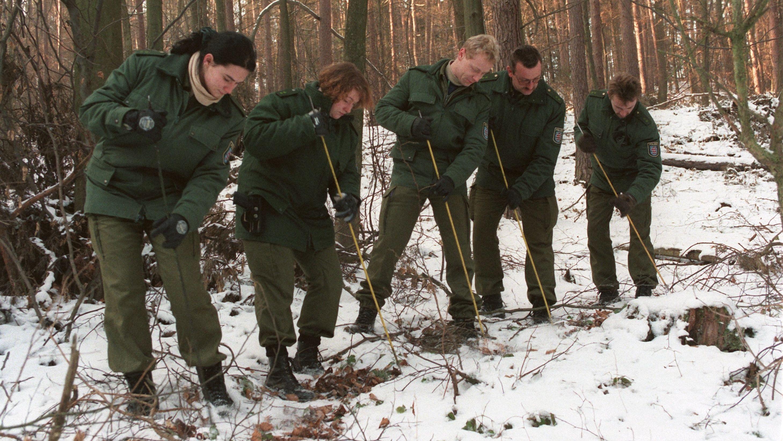 Im Mordfall Ramona durchkämmen Polizisten im Winter ein Waldstück.