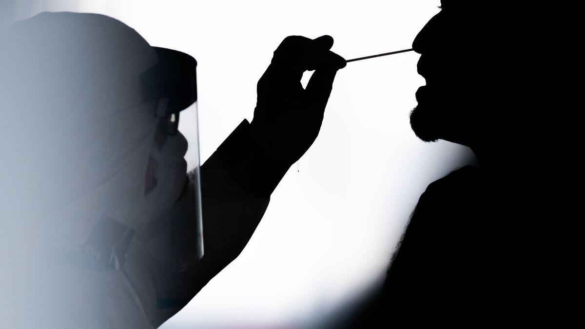 Eine Person in Schutzkleidung macht einen Corona-Test bei einem Mann.