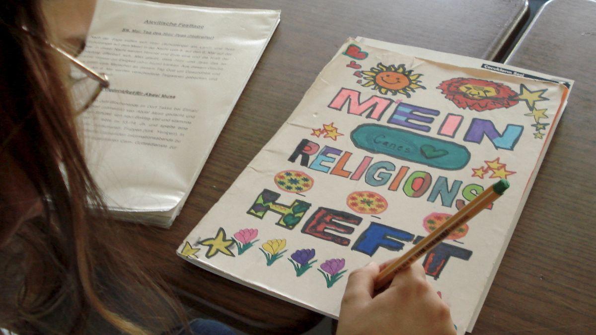 Eine Schülerin bemalt ihr Religionsheft.