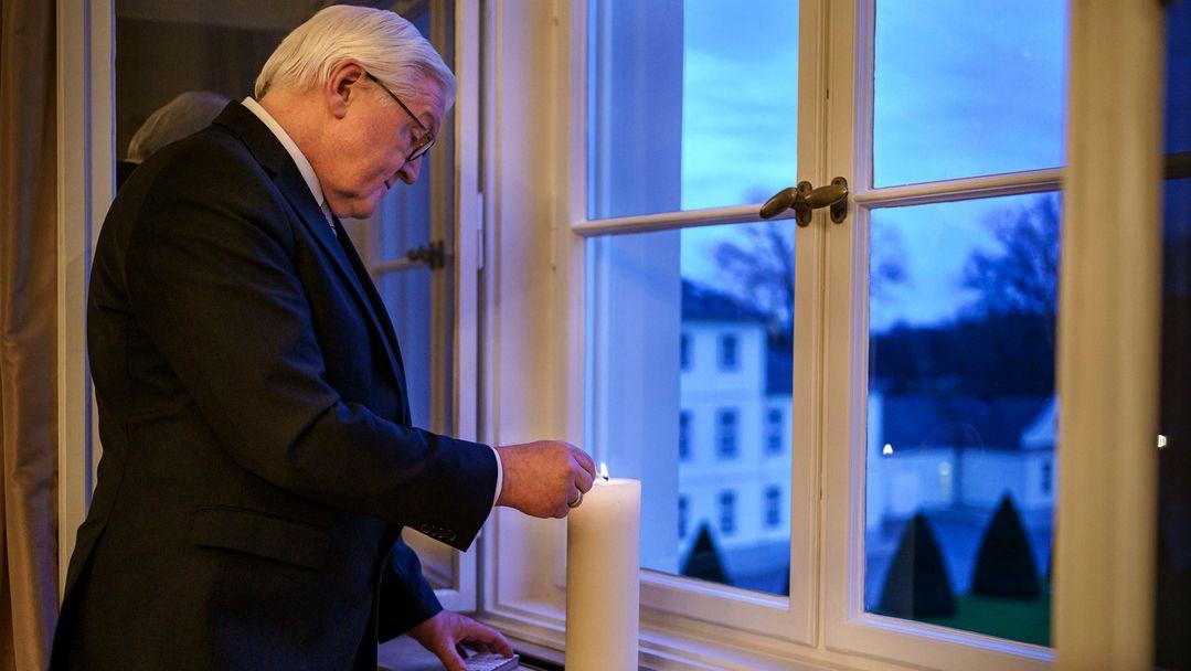 Bundespräsident Steinmeier zündet in einem Fenster von Schloss Bellevue eine Kerze an.