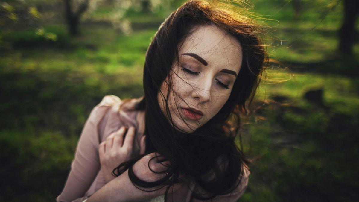 Eine Frau mit langen schwarzen Haaren und rosa Bluse mit geschlossenen Augen im Wind