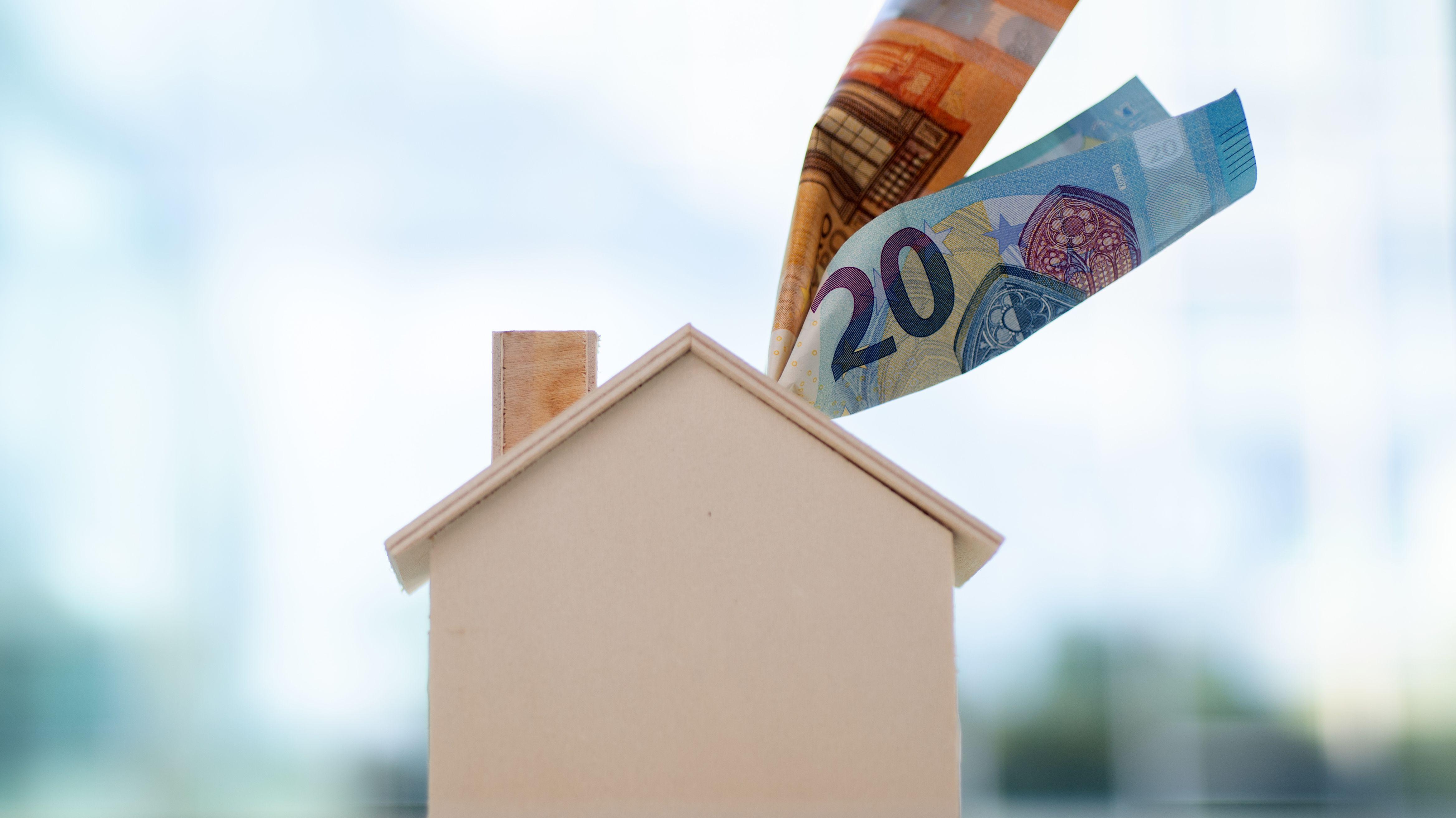 Ein Hausmodell und darin steckende Geldscheine als Symbolbild.