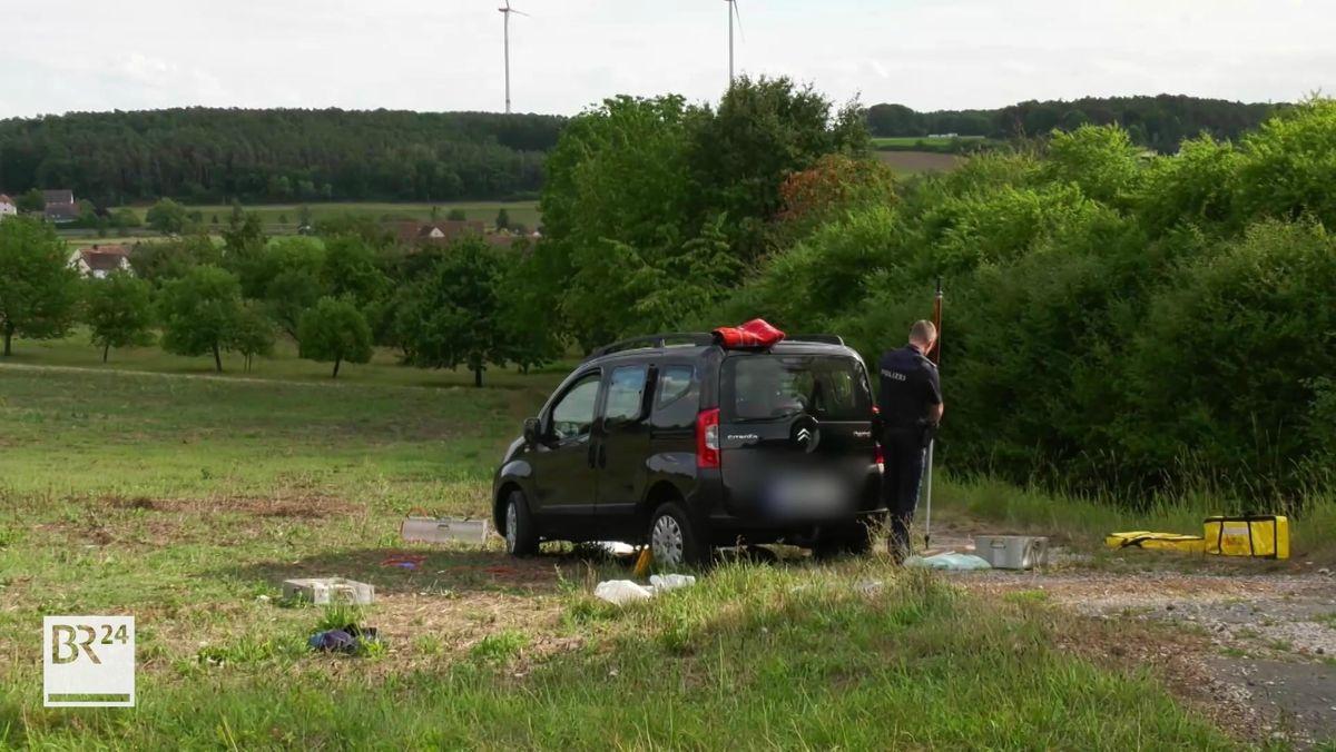 Ein Polizist untersucht das Auto, das auf einem Feldweg steht.