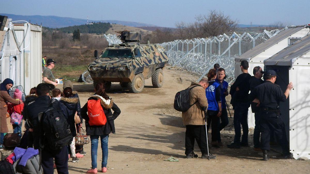 Flüchtlinge an Kontrollstation mit gepanzertem Fahrzeug im Hintergrund