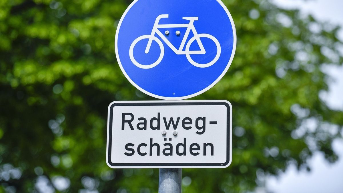 Ein Schild weißt auf Radwegschäden hin.