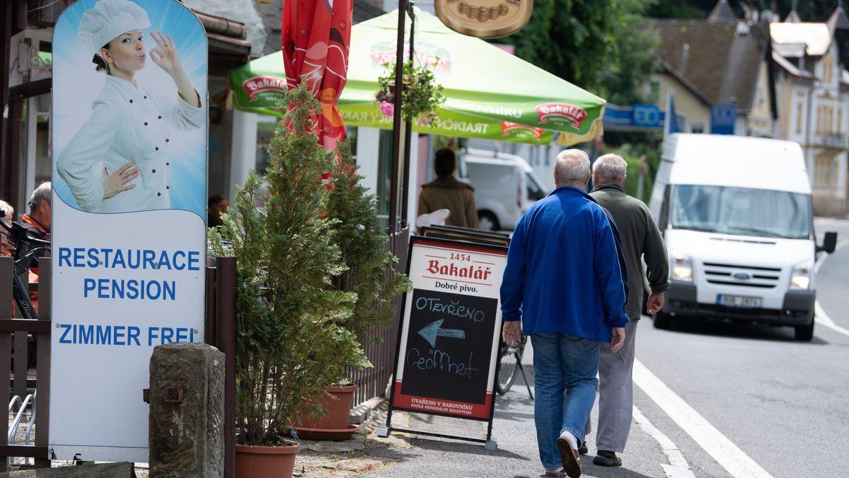 Passanten gehen auf einer Straße in Hrensko (Tschechien) an einem Restaurant vorbei.