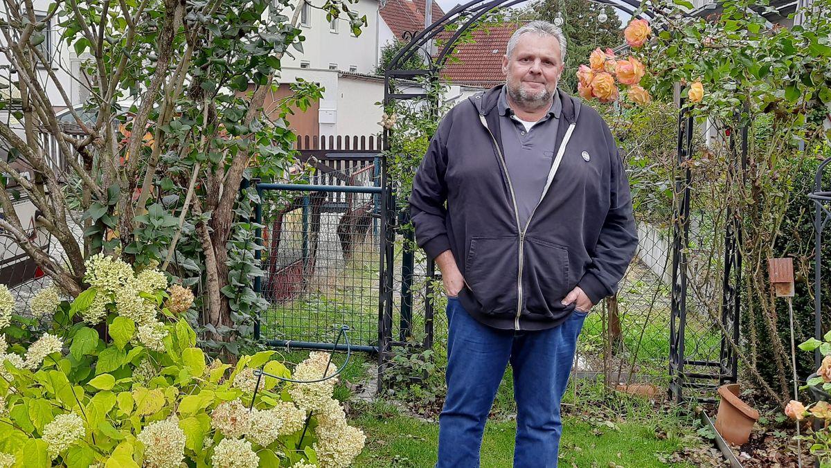 Mann steht in einem Garten