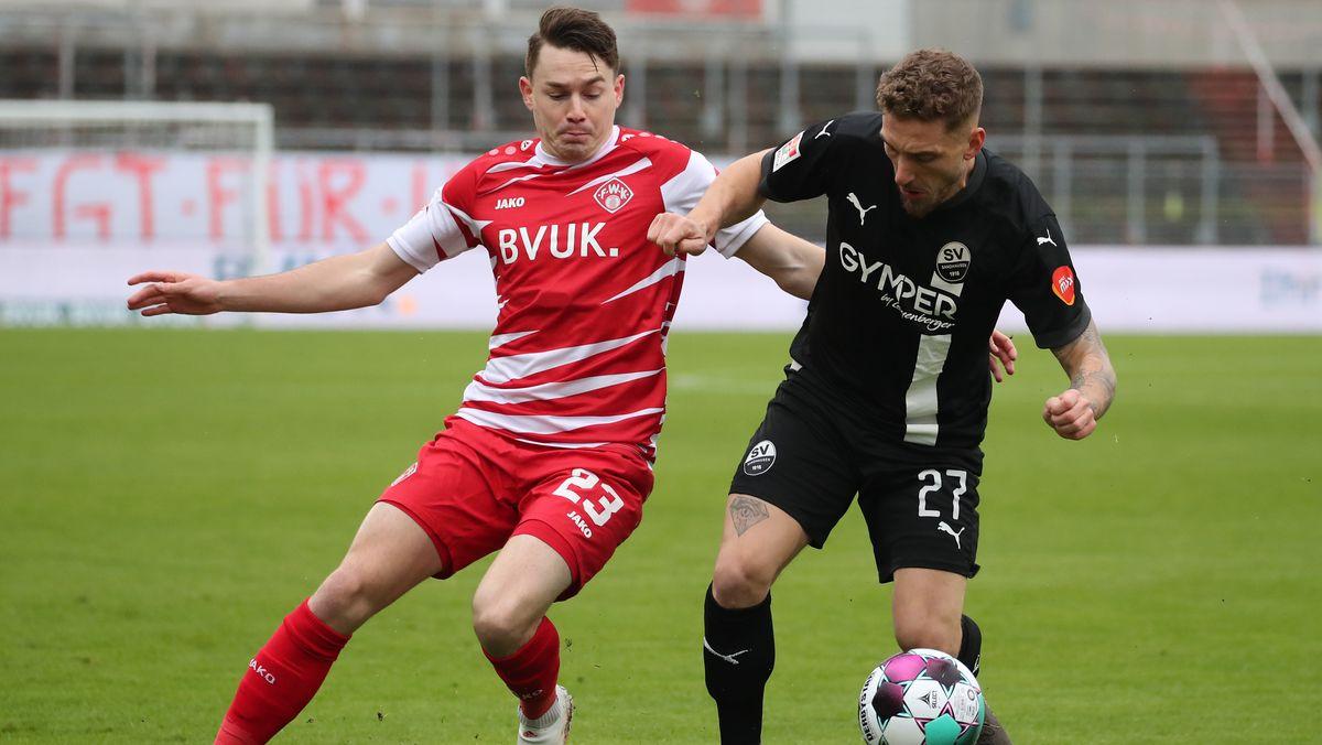 Der Würzburger Florian Flecker (l) kämpft mit Robin Scheu aus Sandhausen um den Ball.