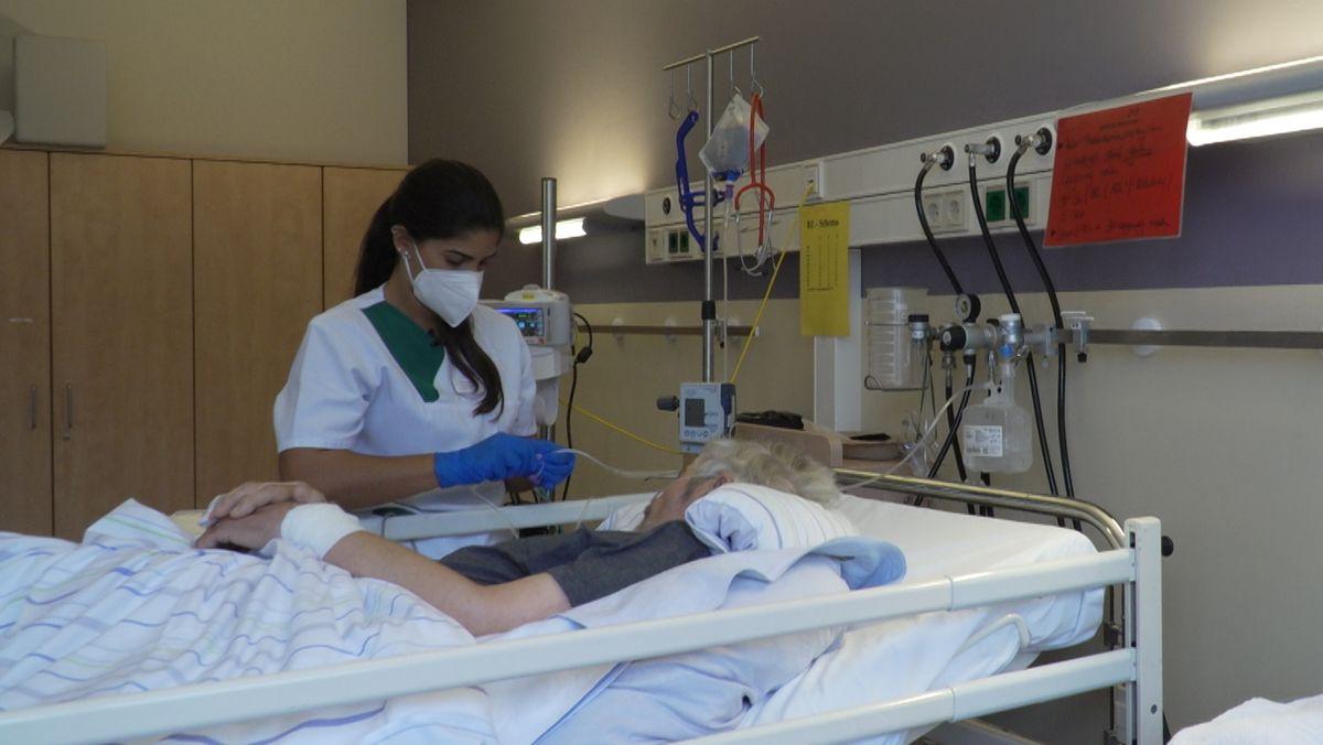 Camilla Medaglia aus Rio kümmert sich an einem Krankenhausbett um einen Patienten.