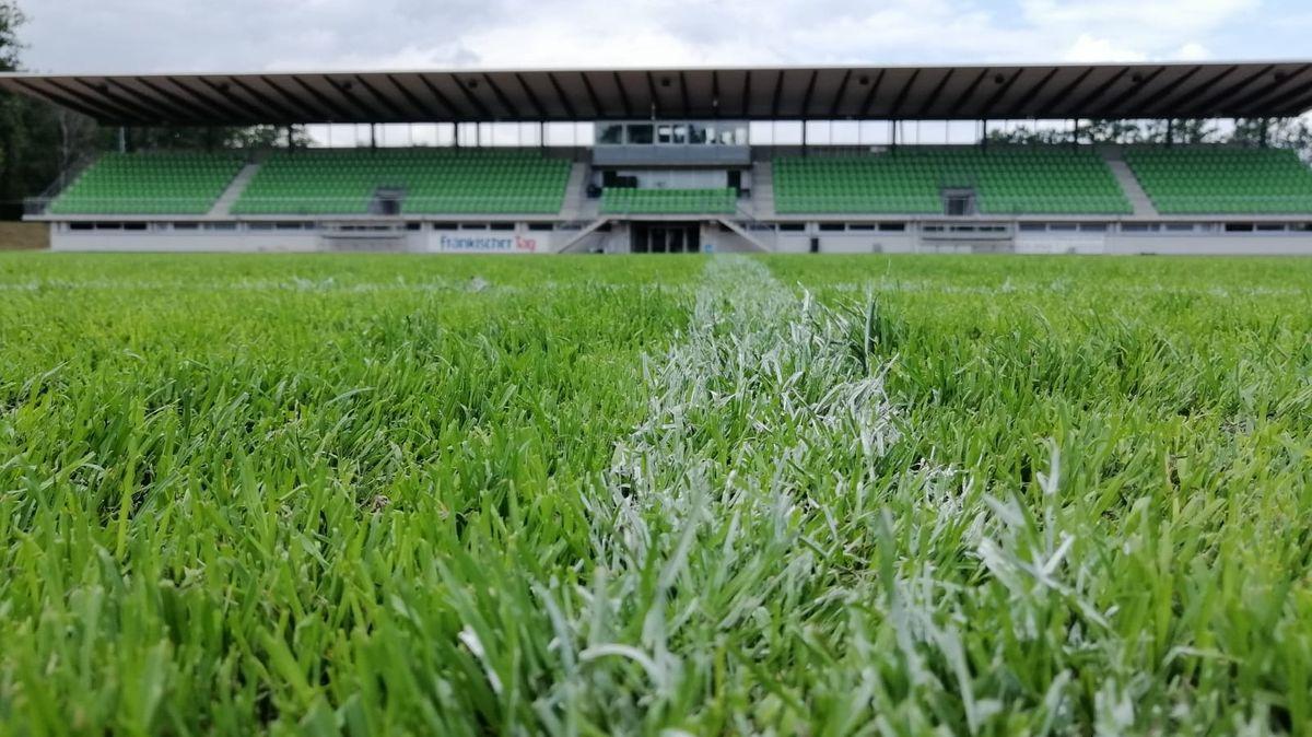 Ein Fußballfeld vor einer leeren Tribüne