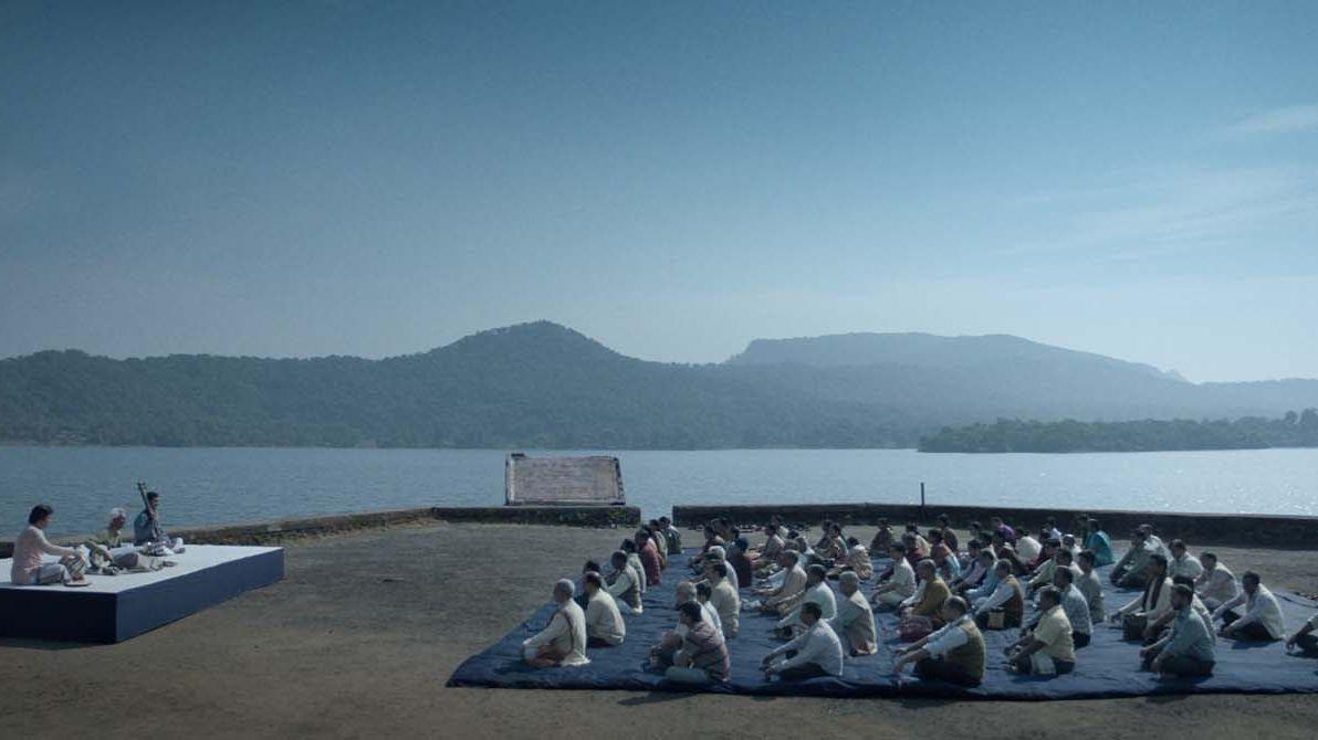 Man sieht drei Musiker auf einer Bühne bei einem Open-Air-Konzert am Meer