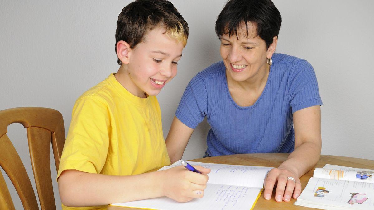 Eine Mutter hilft ihrem Sohn bei den Schulaufgaben