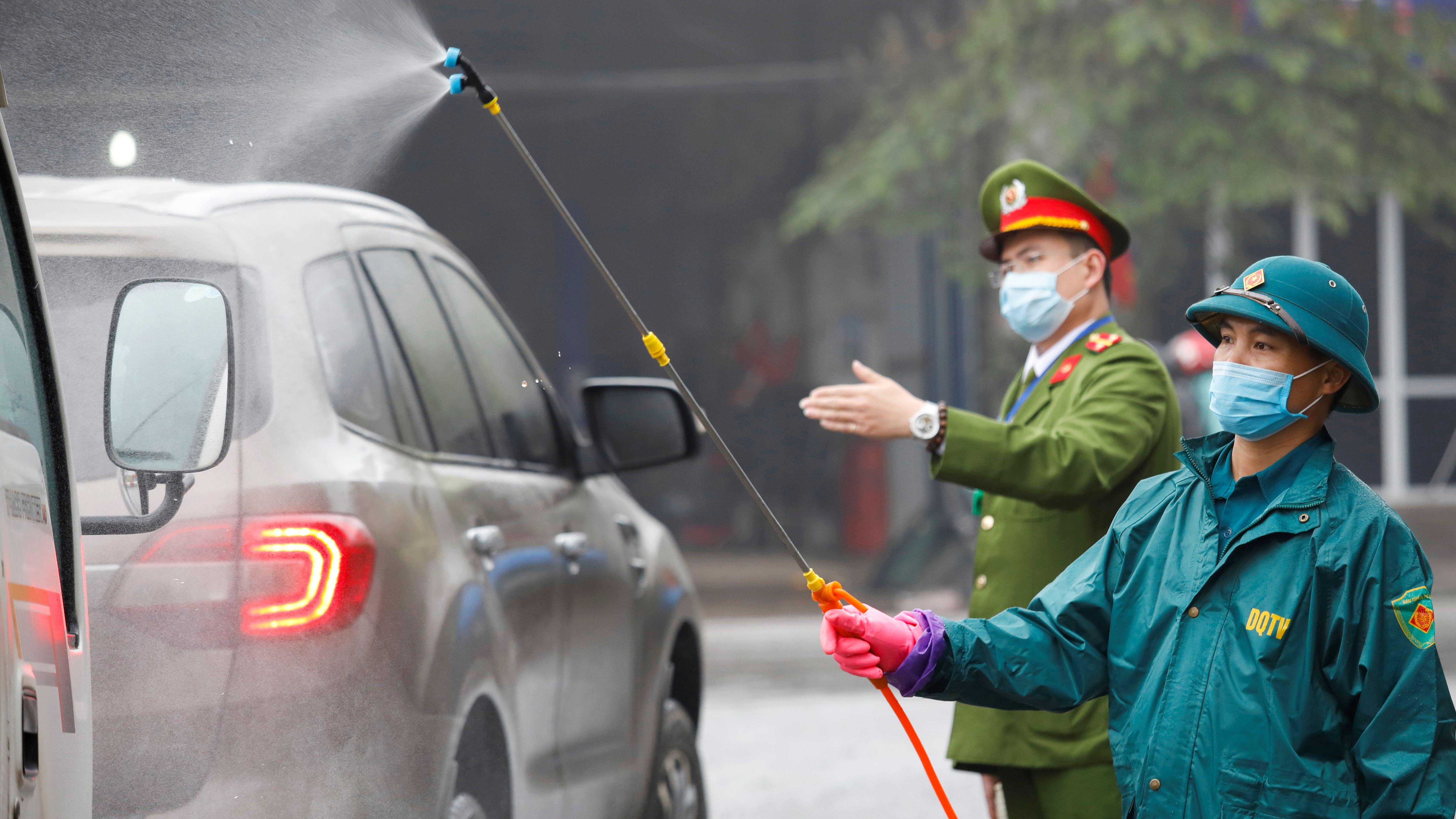 Mitarbeiter des Anti-Coronavirus-Teams in Vietnam sprühen Desinfektionsmittel auf Fahrzeuge in der Provinz Nguyen