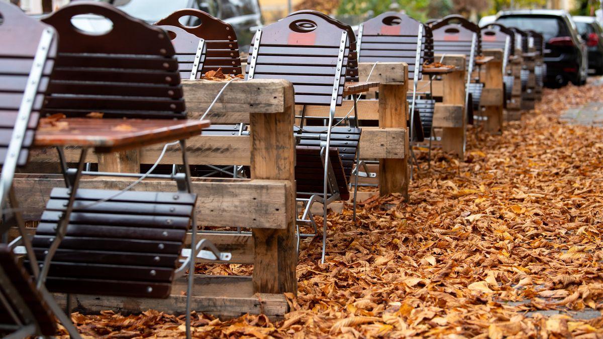 Leere Stühle und Tische stehen im Außenbereich einer geschlossenen Gaststätte.