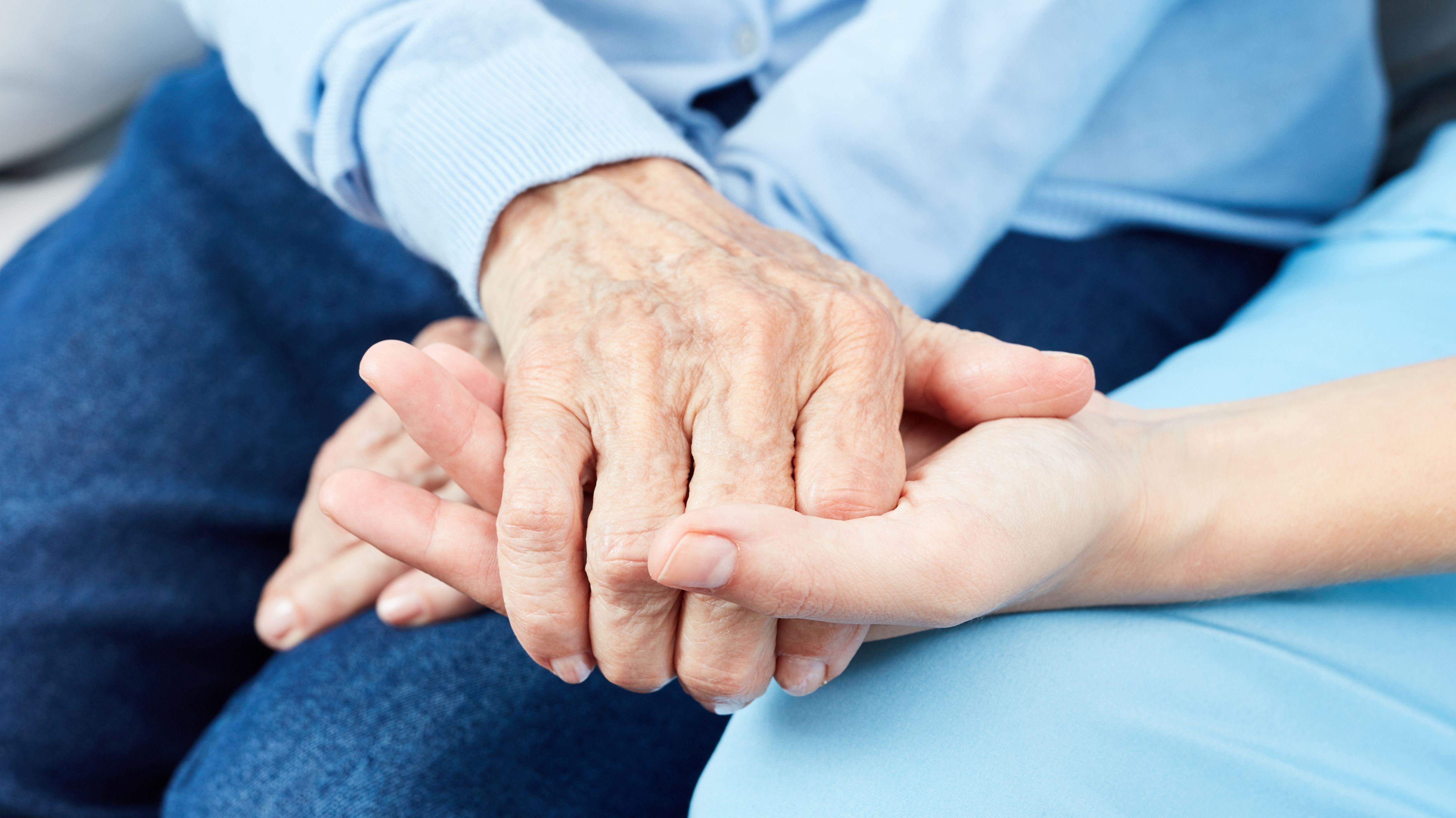 Symbolbild: Pflegerin hält Hand eines Pflegeheimbewohners