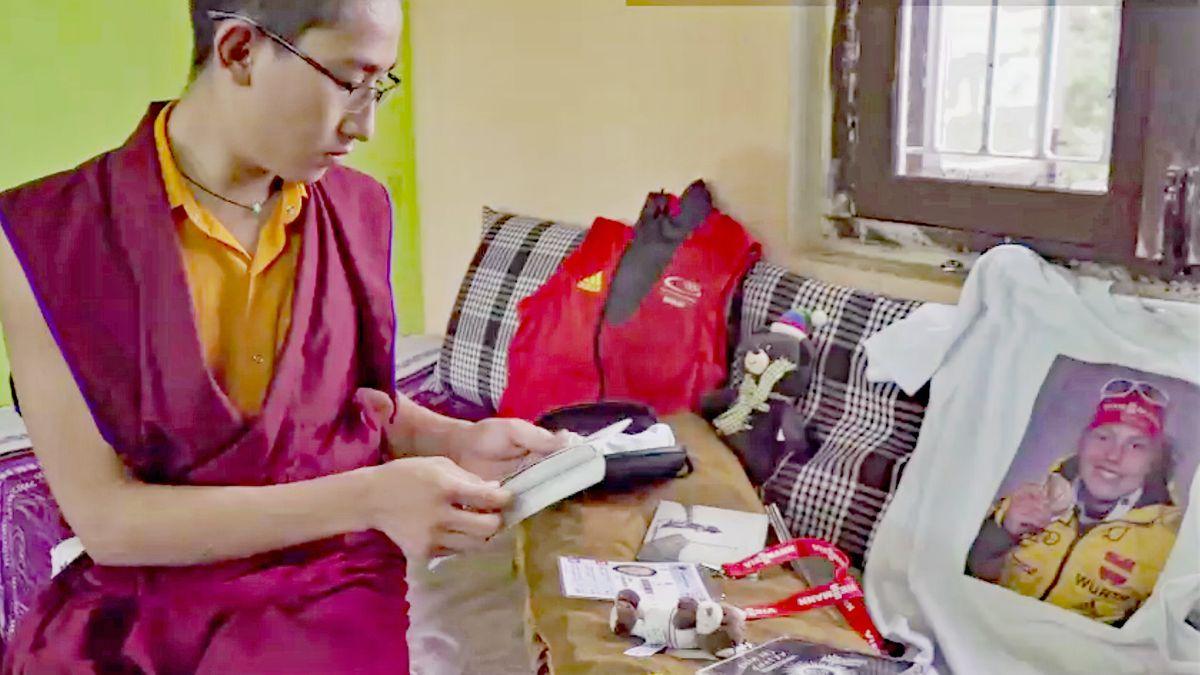 Ein junger mann sitzt auf einem bett und ließt einen Brief.