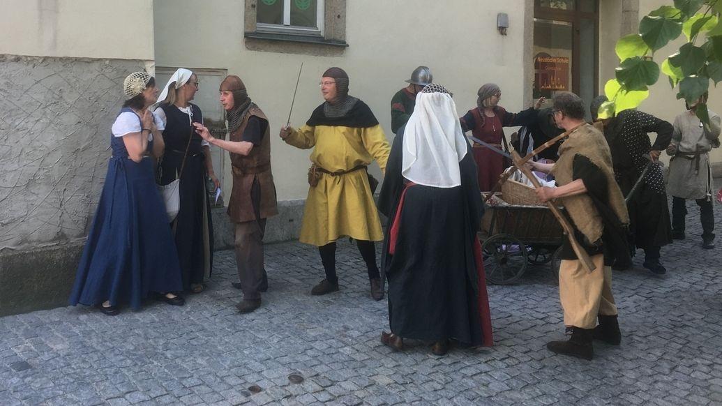 Mehrere Laien-Darsteller in historischen Gewändern stehen in einer Gasse von Hof.