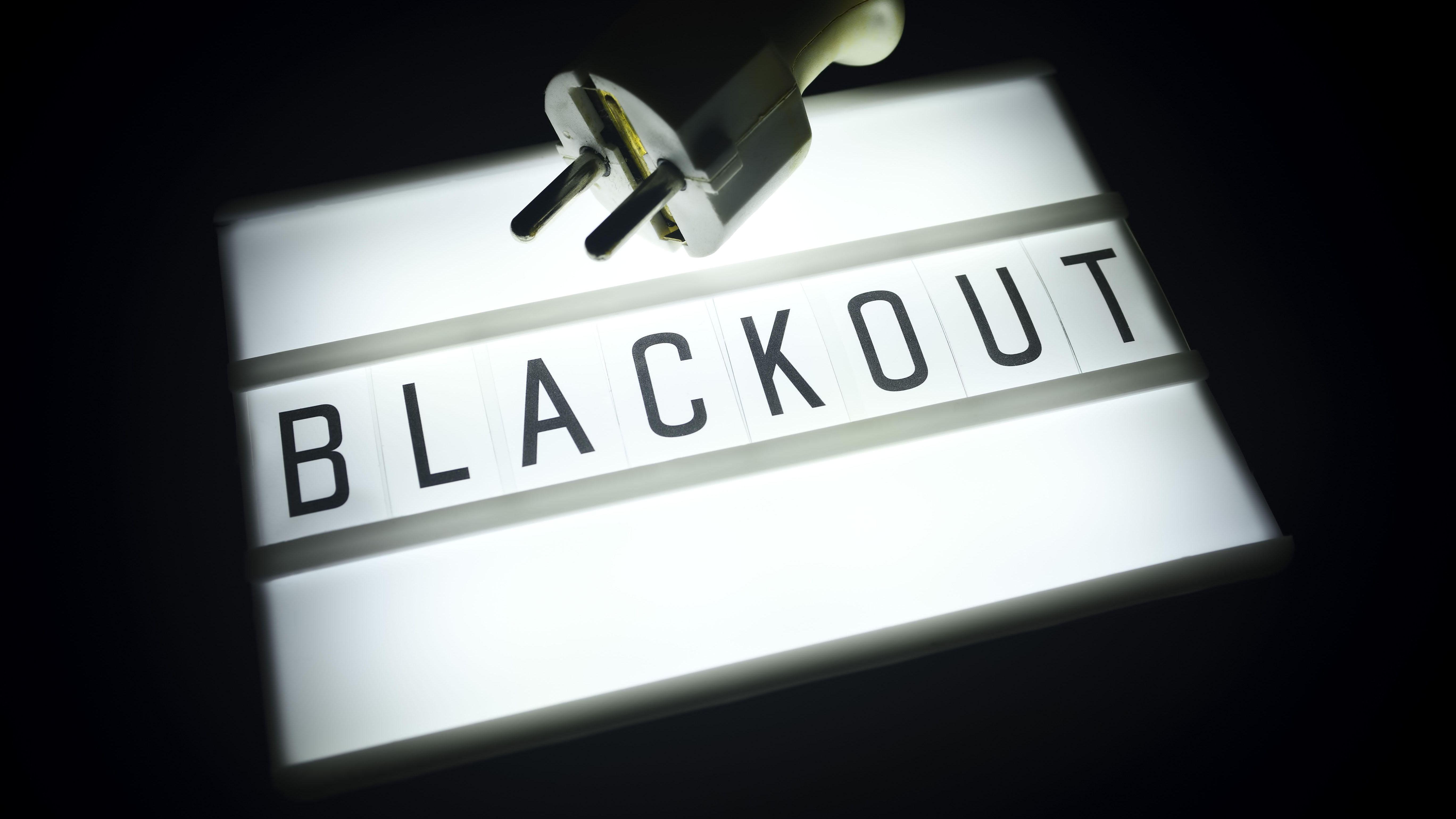 Symbolbild: Leuchttafel mit der Aufschrift Blackout und einem Stromstecker