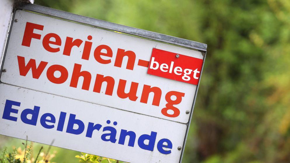 05.05.2021, Bayern, Lindau: Ein Schild an einem Haus weist auf eine Ferienwohnung und Edelbrände hin.