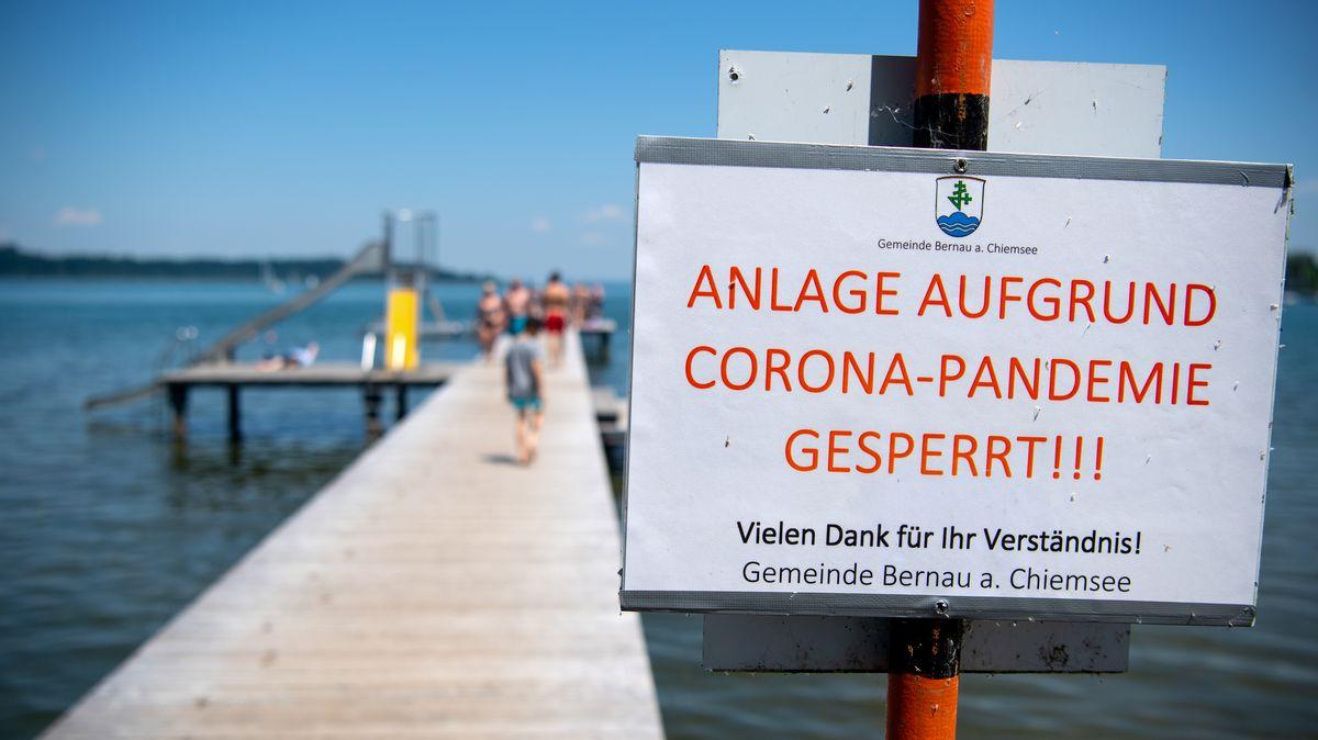 """Ein Schild mit der Aufschrift """"Anlage aufgrund Corona-Pandemie gesperrt"""" ist an einem Steg am Chiemsee zu sehen."""