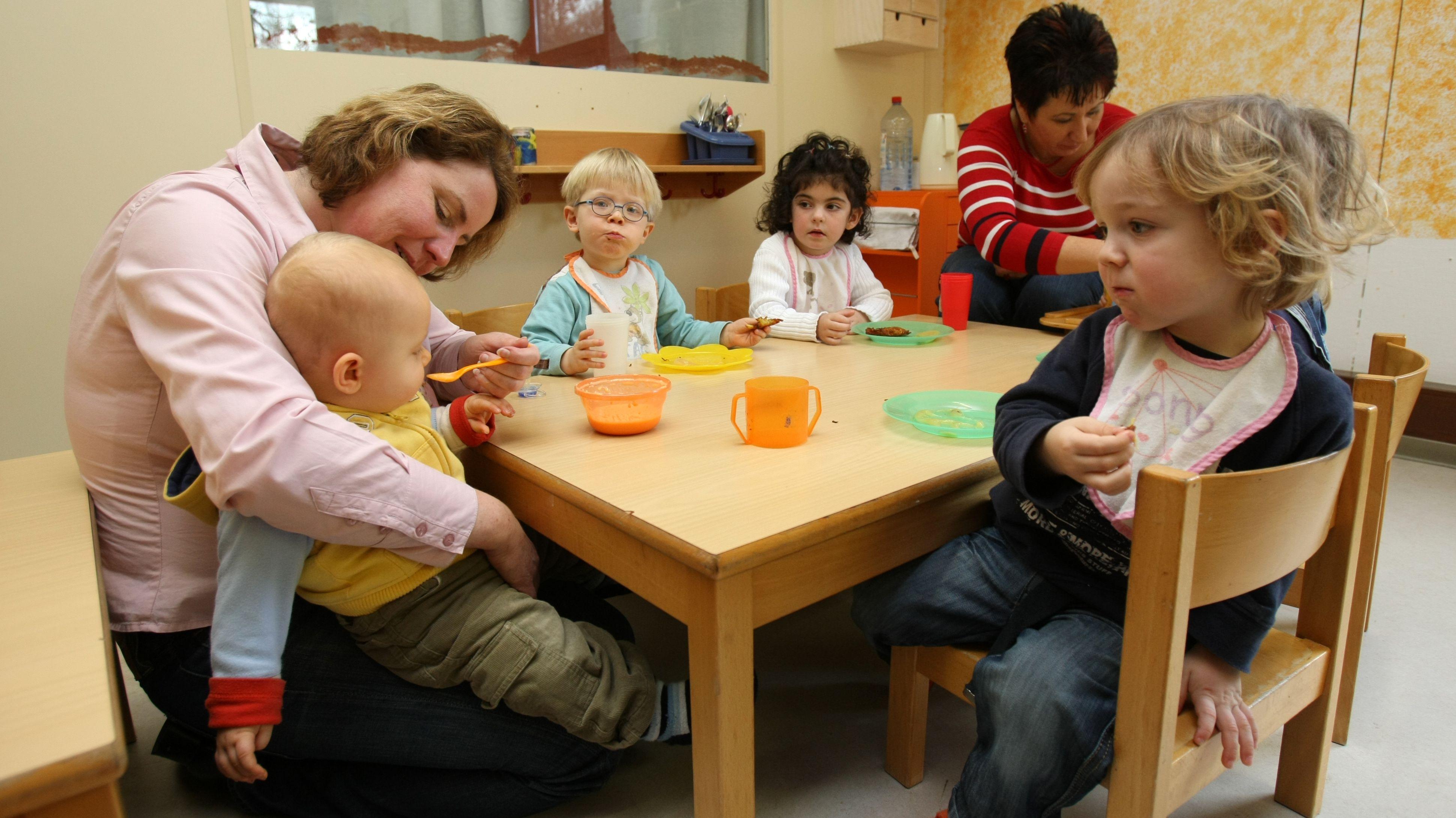 Ein Baby auf dem Schoß einer Erzieherin wird mit Brei gefüttert, daneben sitzen drei andere Kleinkinder und eine weitere Erzieherin am Tisch.