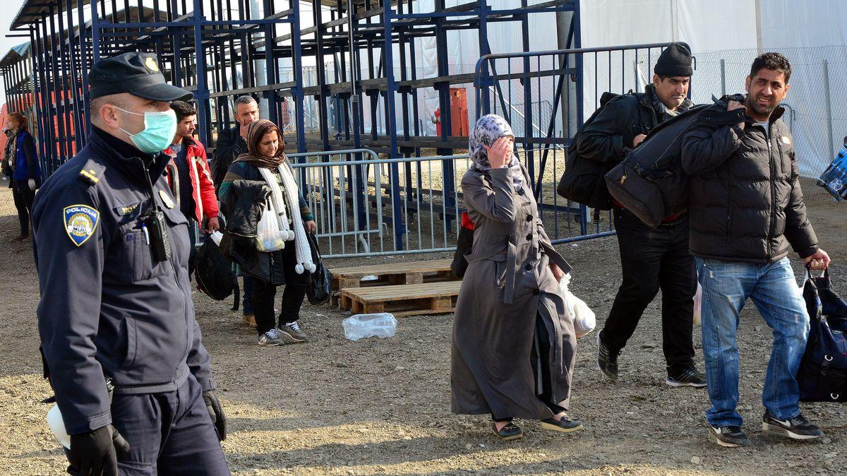 Polizist und Migranten in Slavonski Brod