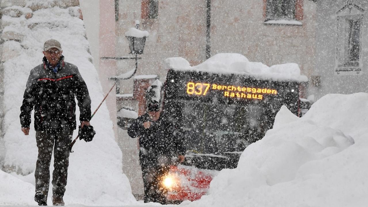 Ein Mann und ein Bus im dichten Schneetreiben in Berchtesgaden (Symbolbild).