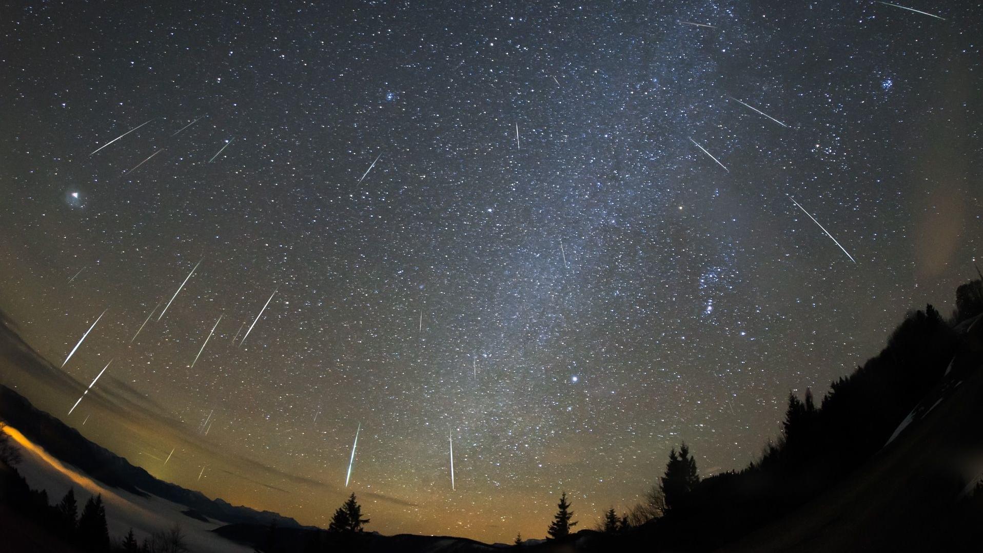 Kompositaufnahme der Geminiden-Meteore zum Maximum des Sternschnuppenstroms. Deutlich ist zu sehen, dass die Sternschnuppen aus dem Sternbild Zwillinge (Mitte am oberen Bildrand) zu kommen scheinen.