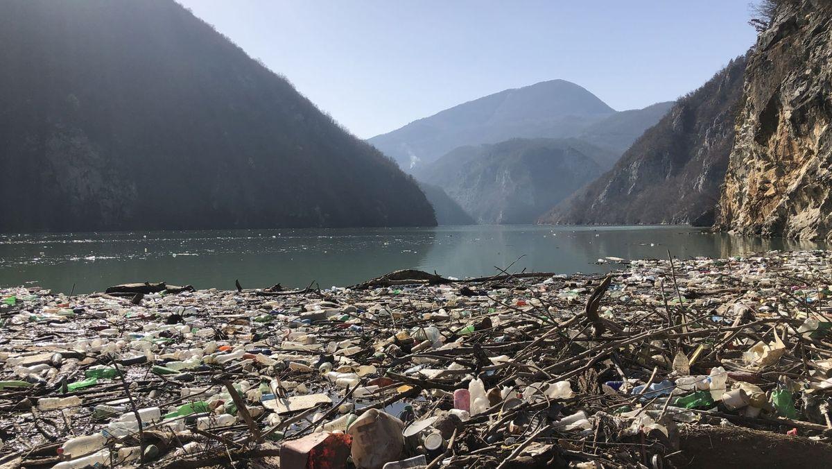 Das Bild zeigt einen Müllteppich auf dem Fluss Drina in Bosnien und Herzegowina. Im Hintergrund sind  die Berge zu sehen.
