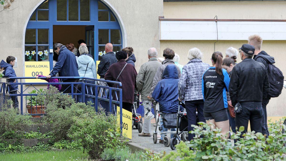 Eine Menschenschlange von hinten vor einem Wahllokal.
