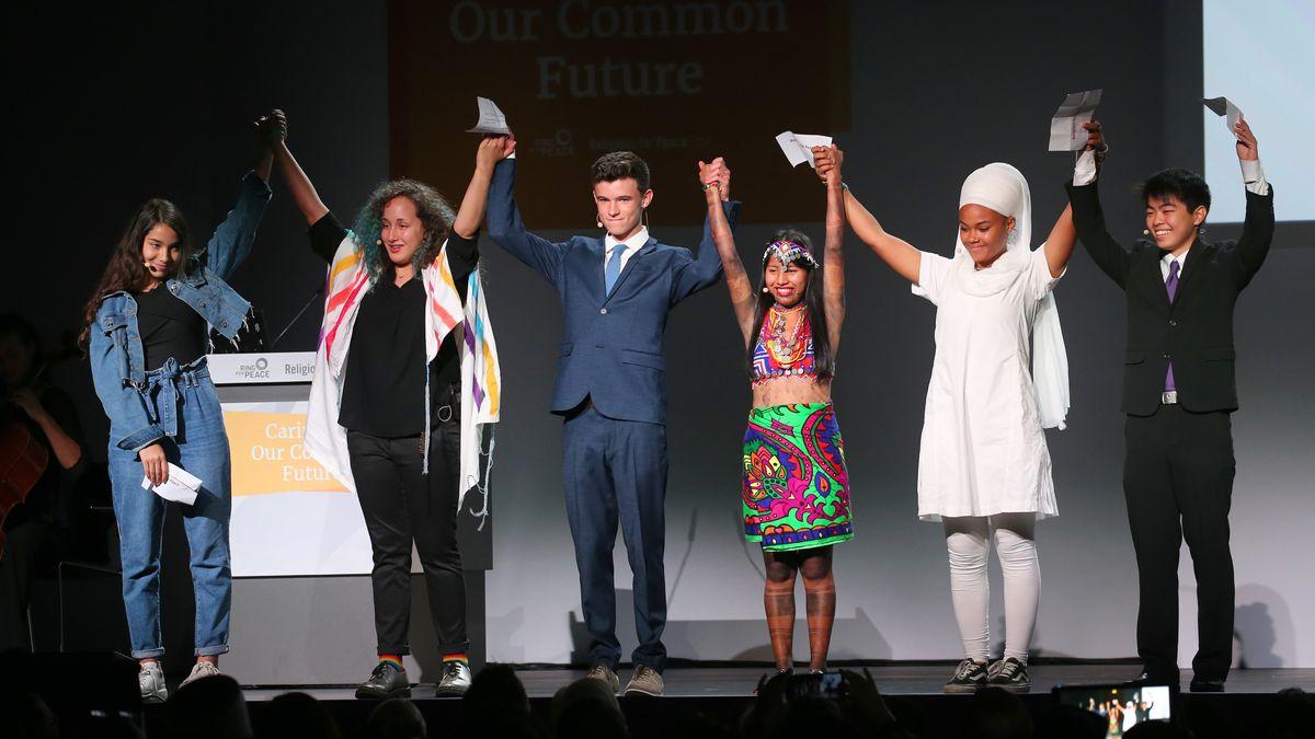 Sechs junge Menschen unterschiedlicher Religionen halten Hände und stehen auf der Bühne