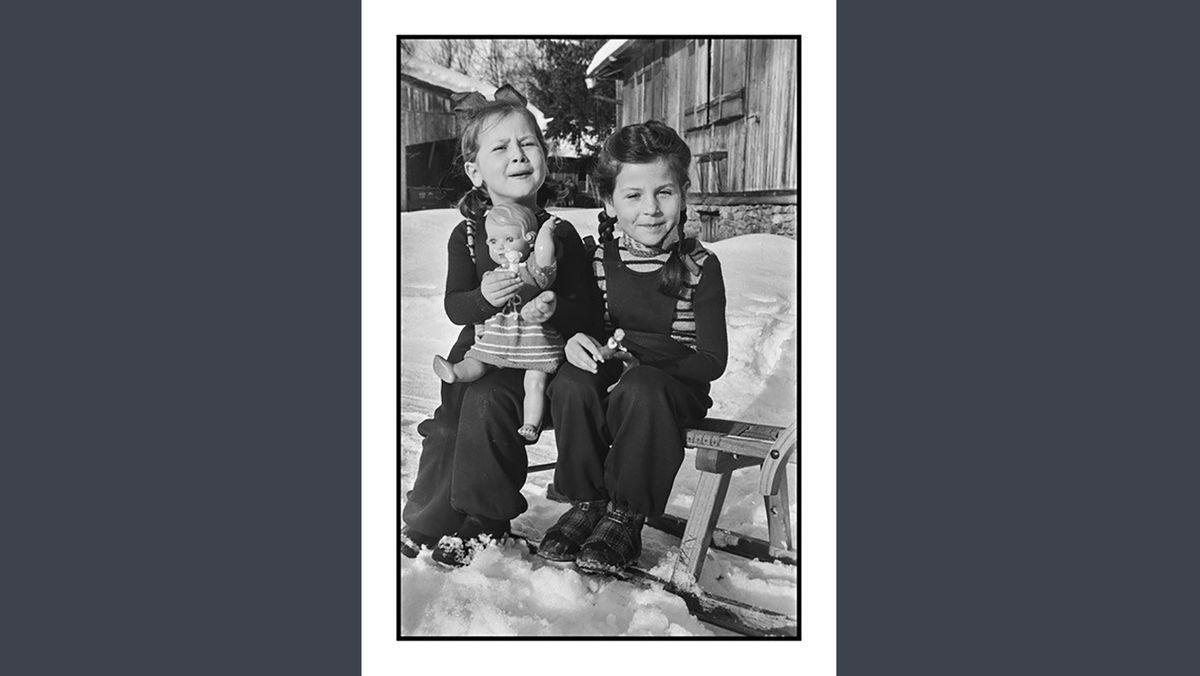 Schwarweißfoto zweier Mädchen auf einem Schlitten