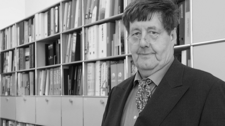 Florian Hufnagl steht vor einem Bücherregal und blickt in die Kamera
