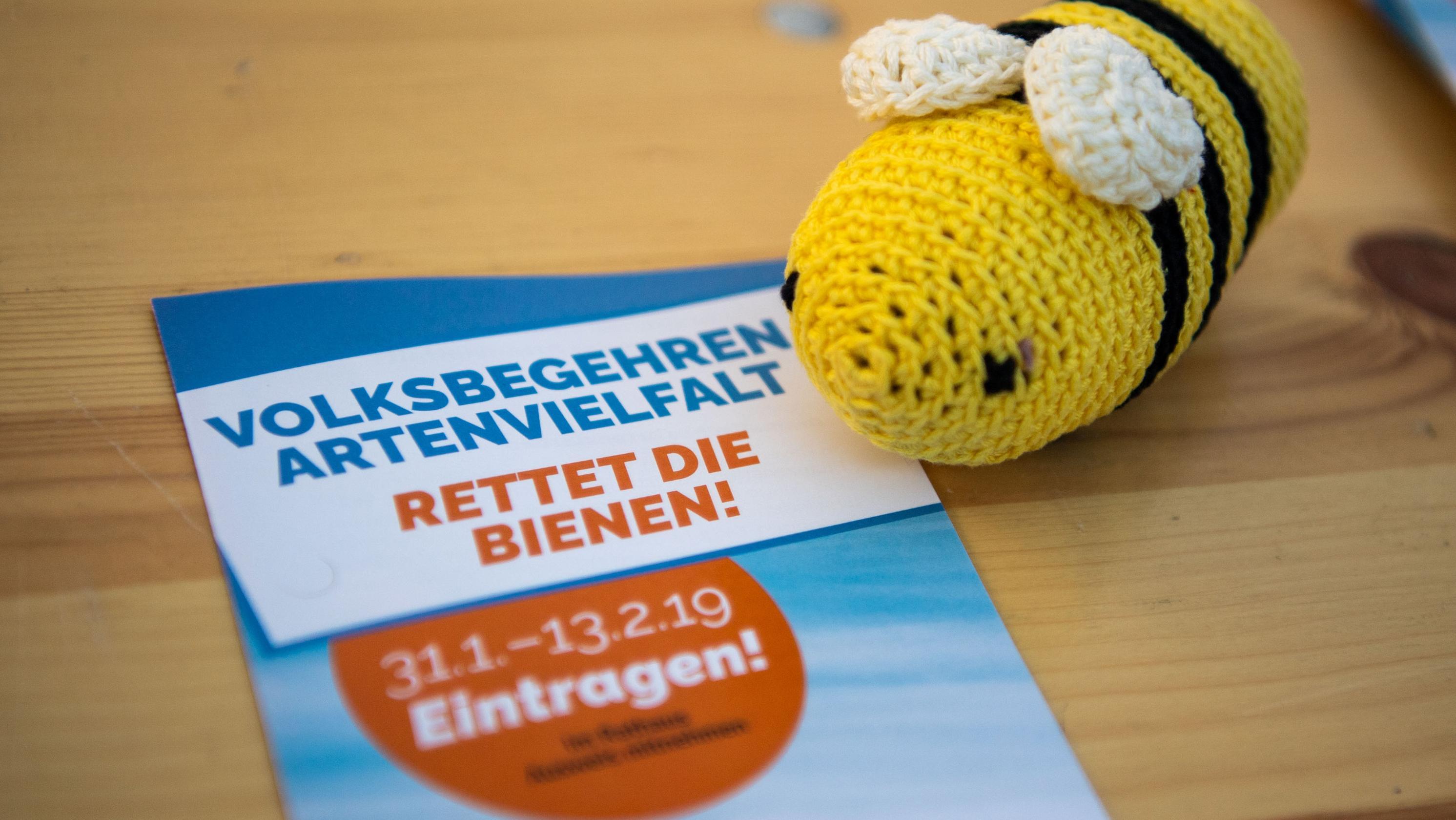 """Eine Wollbiene neben dem Werbeplakat für das Volksbegehren """"Artenvielfalt""""."""